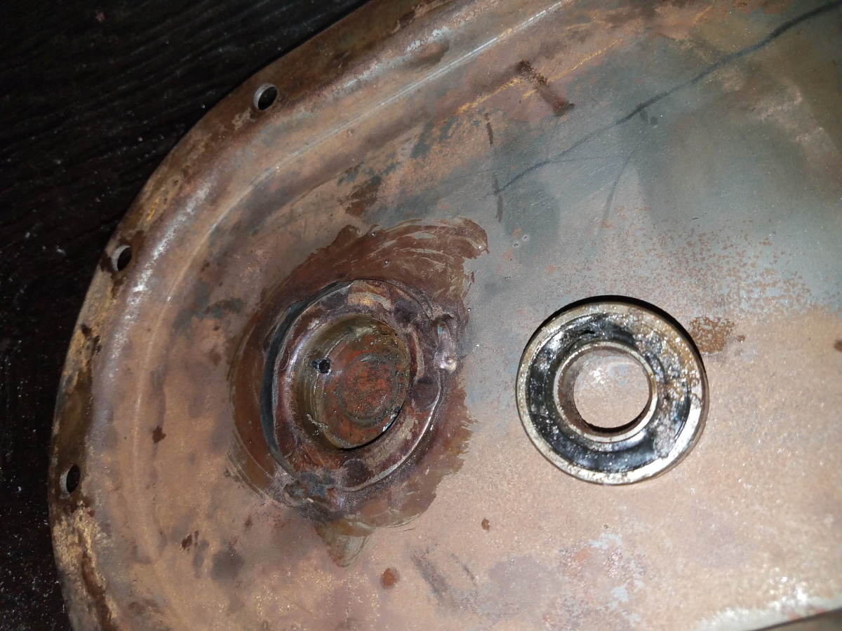 Old bearing shown, removed from bearing cup on right-hand side plate