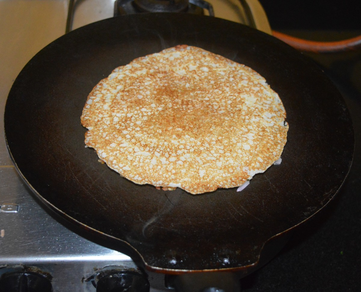 Press it a little with a spatula. Add half a teaspoon of oil on the top. Cook on medium heat until the bottom becomes golden brown. Flip it. Add half a teaspoon of oil on the top. Let the other side also become golden brown.