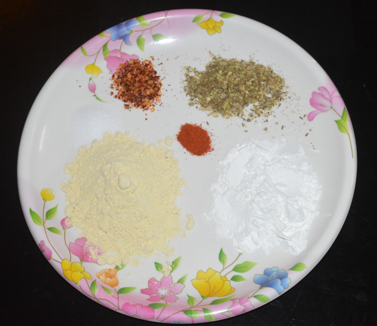 Add gram flour, cornflour, crushed cumin-coriander seeds, chili flakes, red chili powder, and salt.