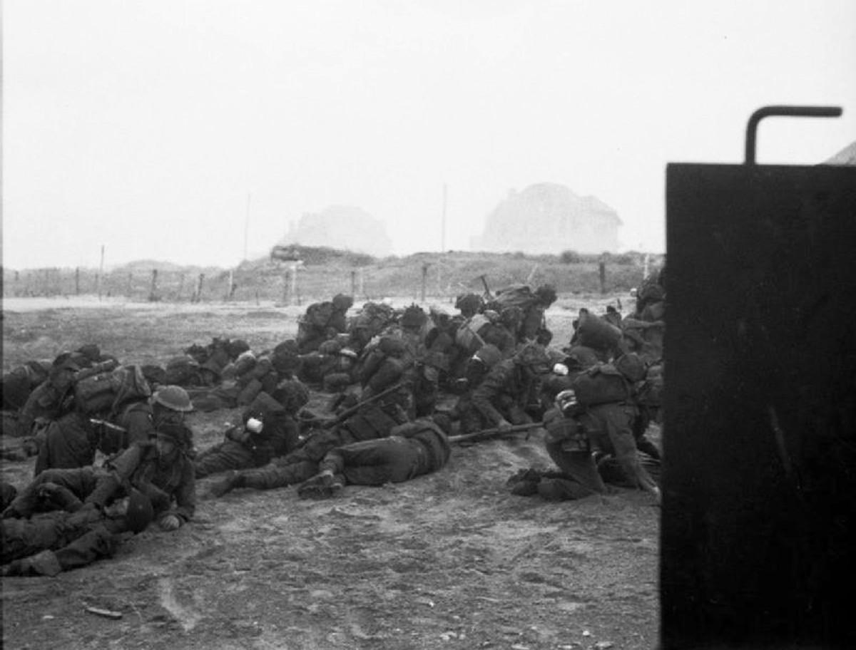 British troops under German artillery take cover after landing on Sword Beach.