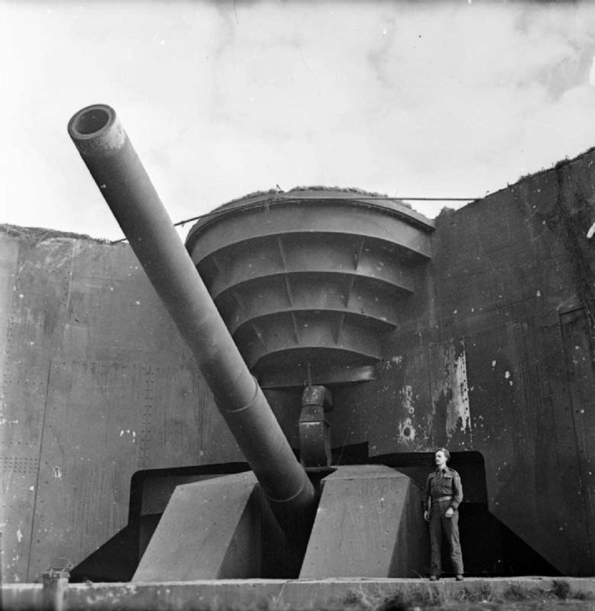 A British soldier poses next to the recently captured German 380 mm gun Todt Battery at Cap Gris Nez soon after D-Day landings.