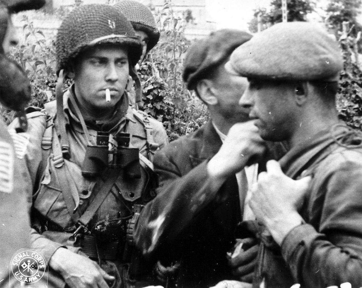 A member of the American 82nd Airborne division meets with members of the French resistance on D-Day.