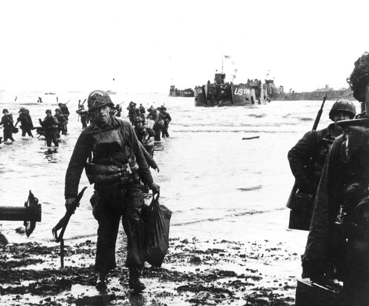 """Carrying their equipment, US assault troops move onto Utah Beach. Landing craft can be seen in the background. Among them would be J.D. Salinger the author of """"The Cather in the Rye."""""""