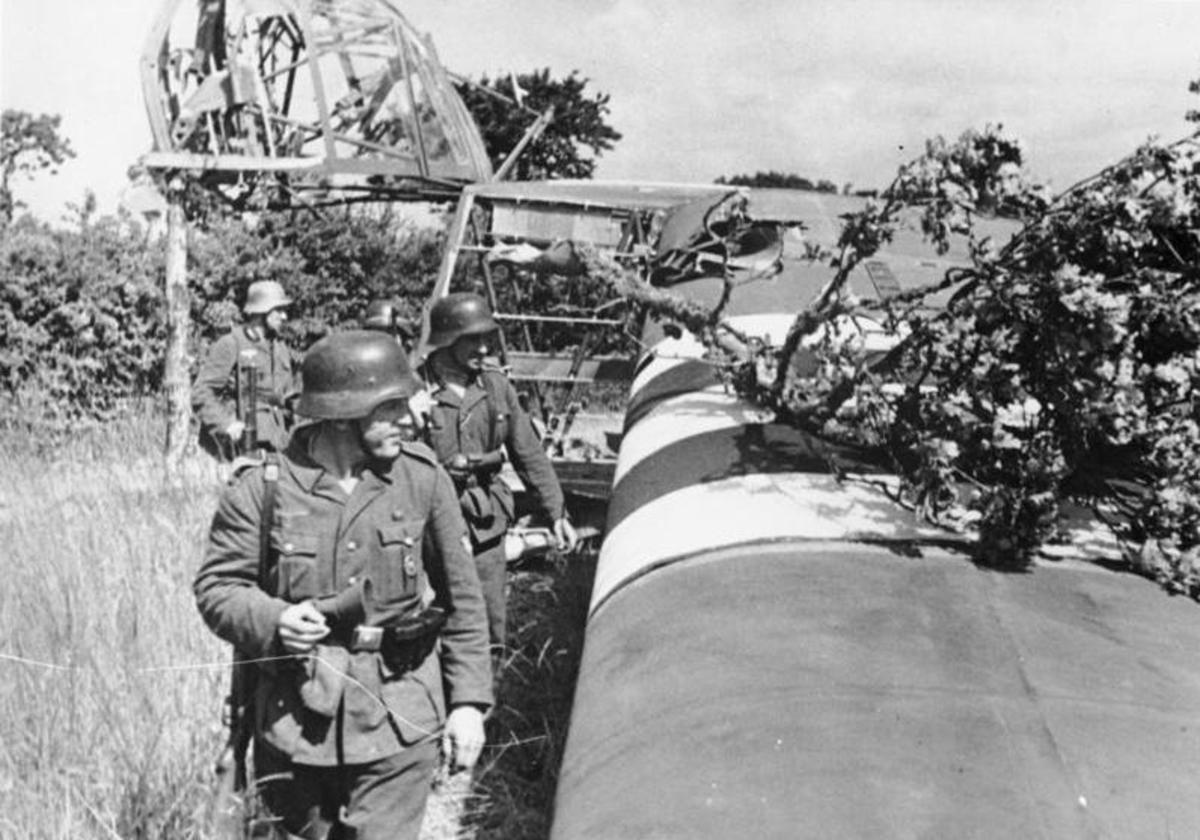 An abandoned Waco CG-4 glider is examined by German troops the morning of the D-Day landings.