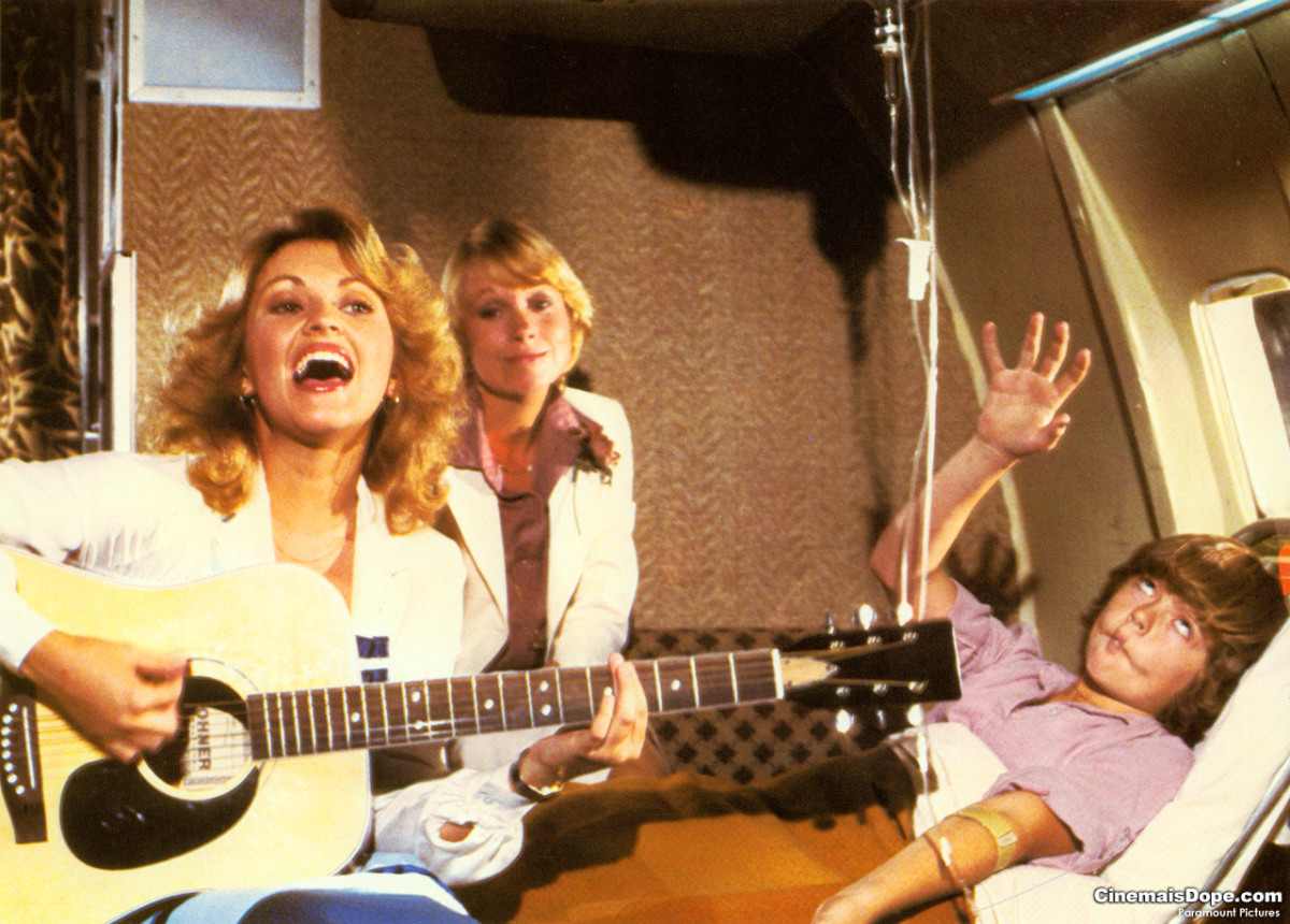 Lorna Patterson comforts sick Jill Whalen with her sky high singing in Airplane! as Joyce Bulifant listens in
