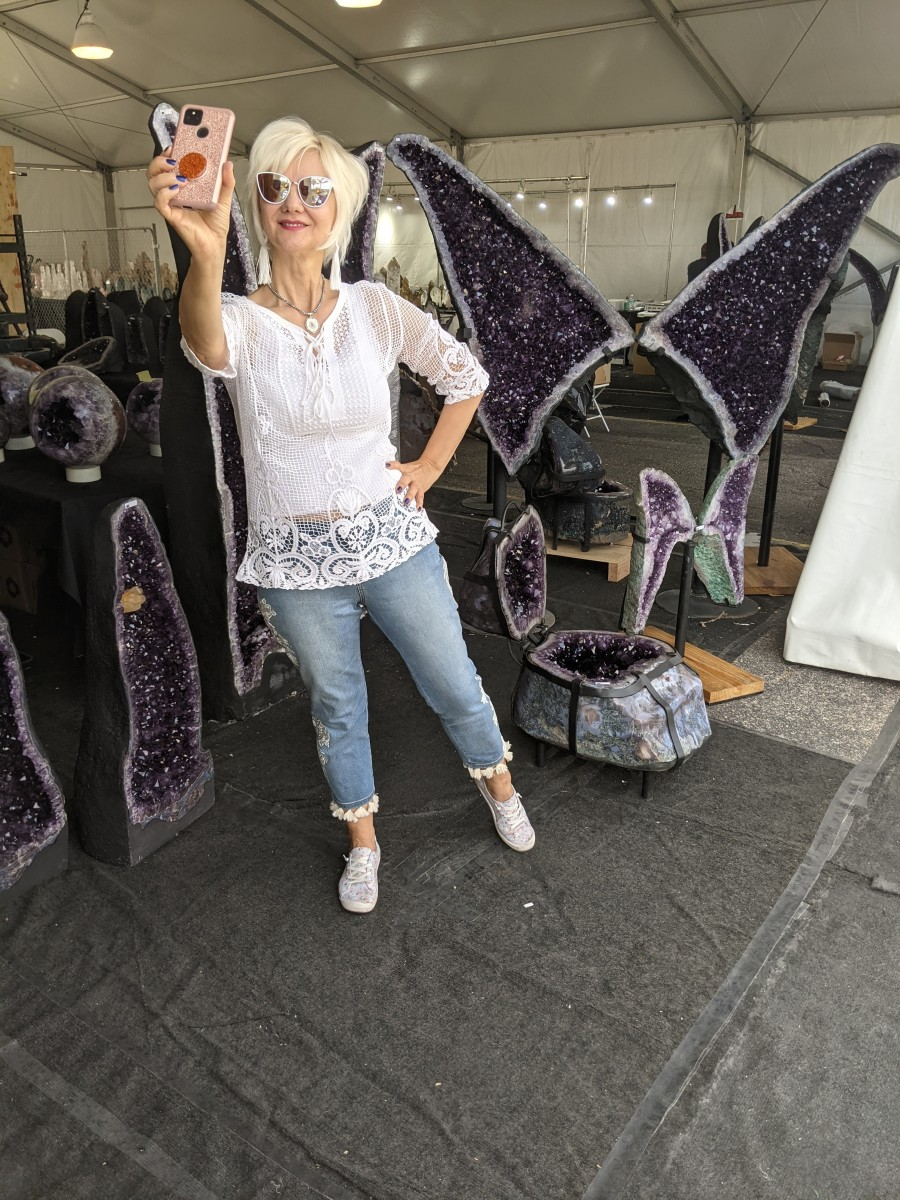 My at the annual Tucson Gem & Mineral Show  taking a selfie in front of a room full of large geodes with amethyst crystals growing inside them