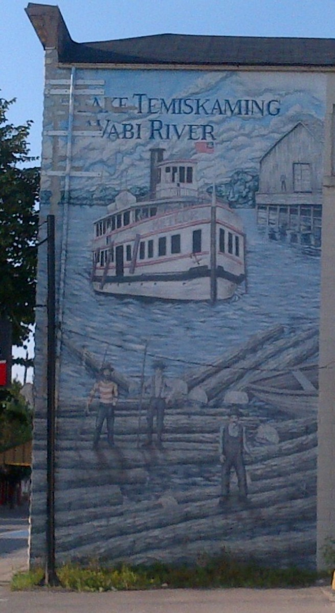 Photograph of the mural on the side of a building on Armstrong Street, New Liskeard, Ontario, Canada, just south of the Wabi River. Photo taken in August 2018.
