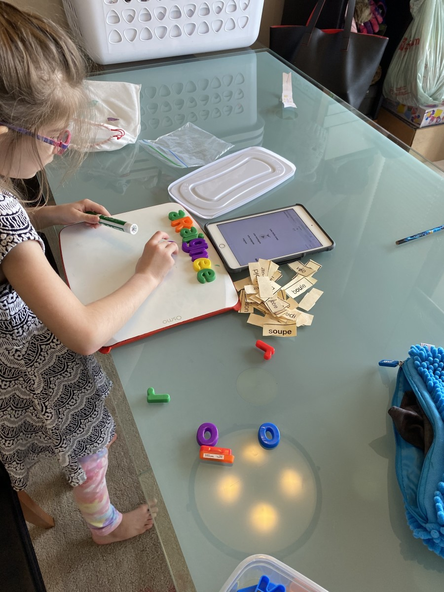 """My daughter working on her own after school with our """"tools"""" to learn her reading and writing.  20 minutes a day can be fun and makes a big difference. Note the ordinary """"tools"""", white board, alphabet letters.  Things many parents already have."""