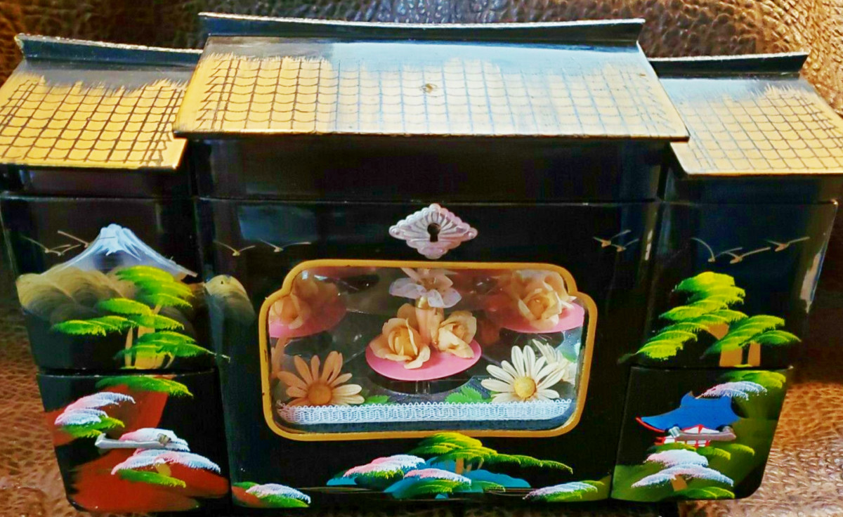 """This lovely made in Japan jewelry box has a beautiful dancer inside. She dances to the music played from the music box inside the cabinet. 13"""" wide 9.25"""" high 6.75"""" deep."""