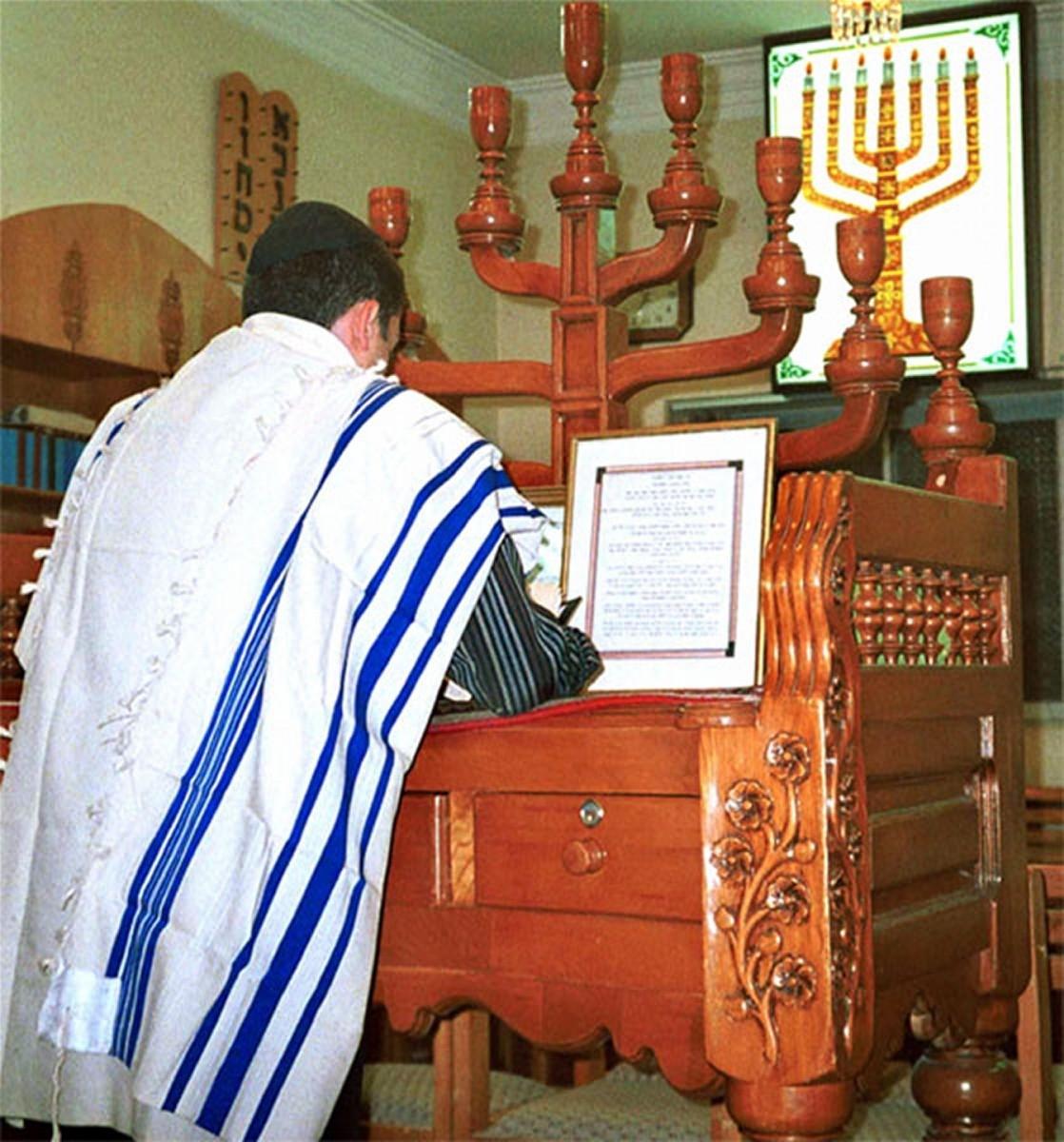A man wearing a tallit, a traditional Jewish prayer shawl while worship.