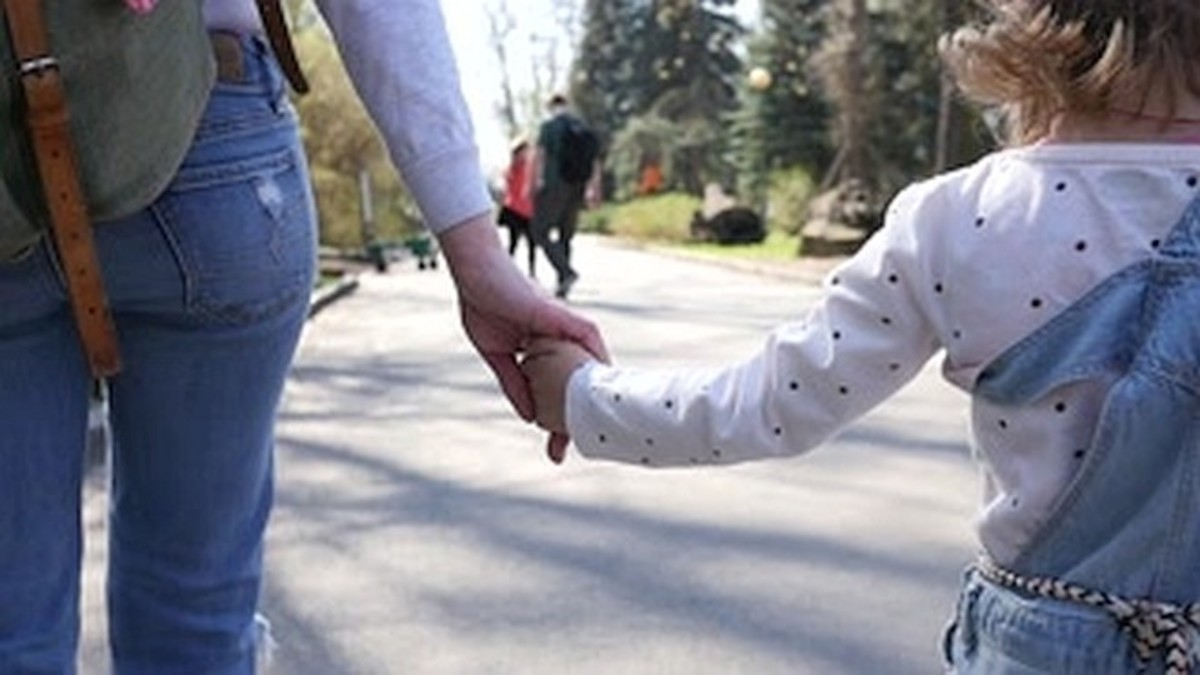 A child feels safe while holding mother's hand