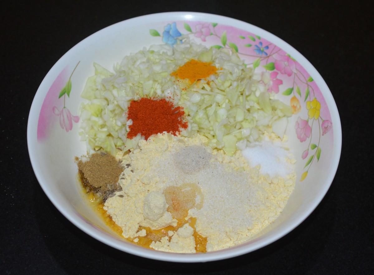 Step one: Add gram flour, semolina, chopped cabbage, turmeric powder, asafoetida powder, cumin-coriander powder, red chili powder, oil, sugar (optional), and salt to a mixing bowl.