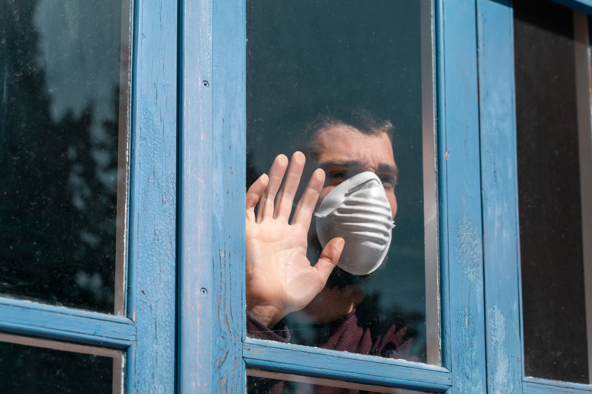 Description: A man with a sad expression wearing a COVID-19 face mask looking out of a window.