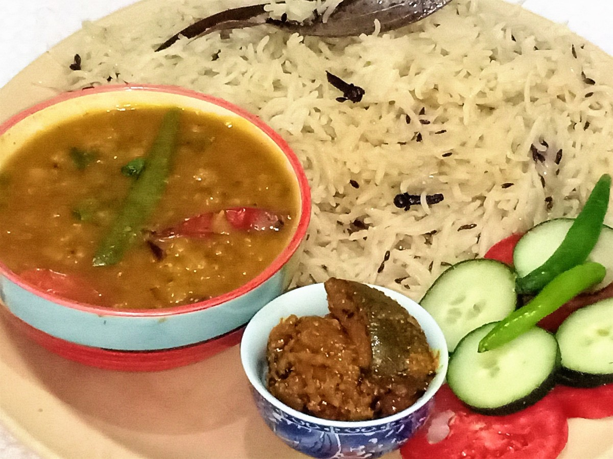 Dal chawal (lentils and rice) served with salad and mango pickle