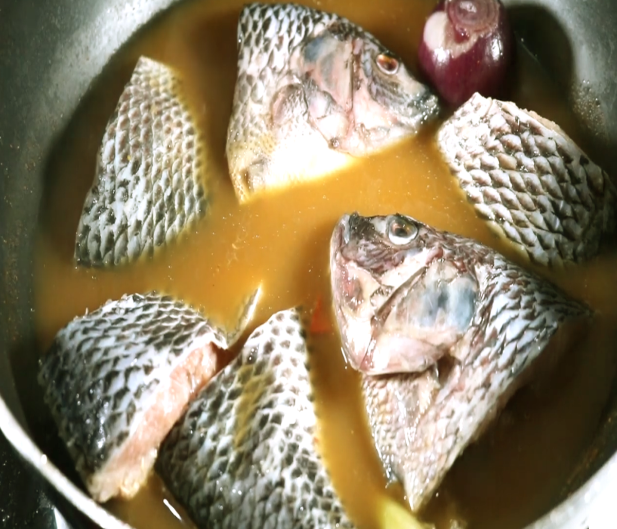 Add in the fish into the pot to cook with the boiled seasonings and spices