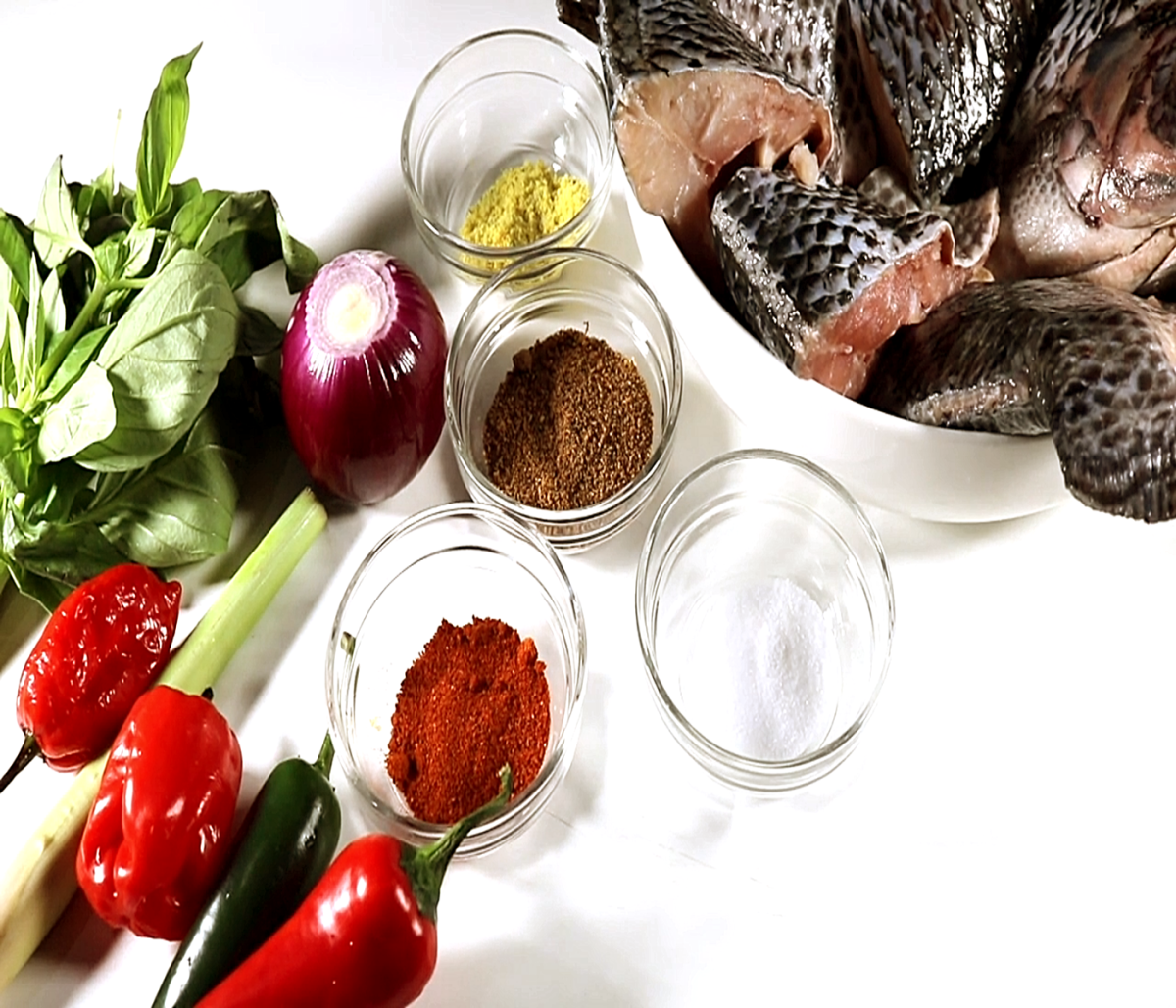 Clockwise from bottom to top – Red chilies, green bird's eye chilies, scotch bonnet peppers, lemongrass, fresh bay leaf, red onion, spices and seasonings, and Tilapia fish