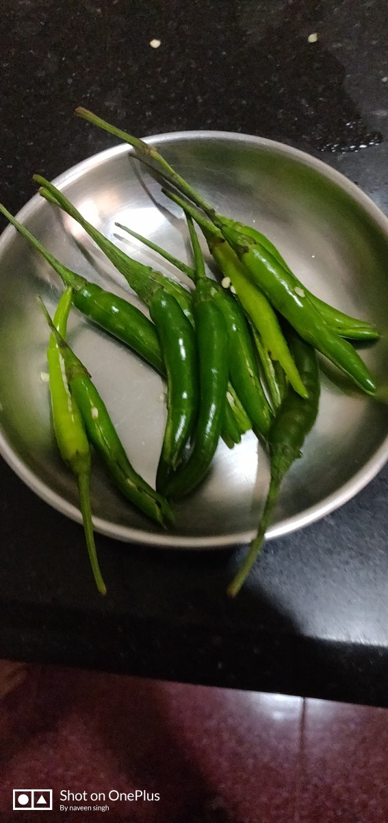 Slit spicy green chillies & fry it in the oil.