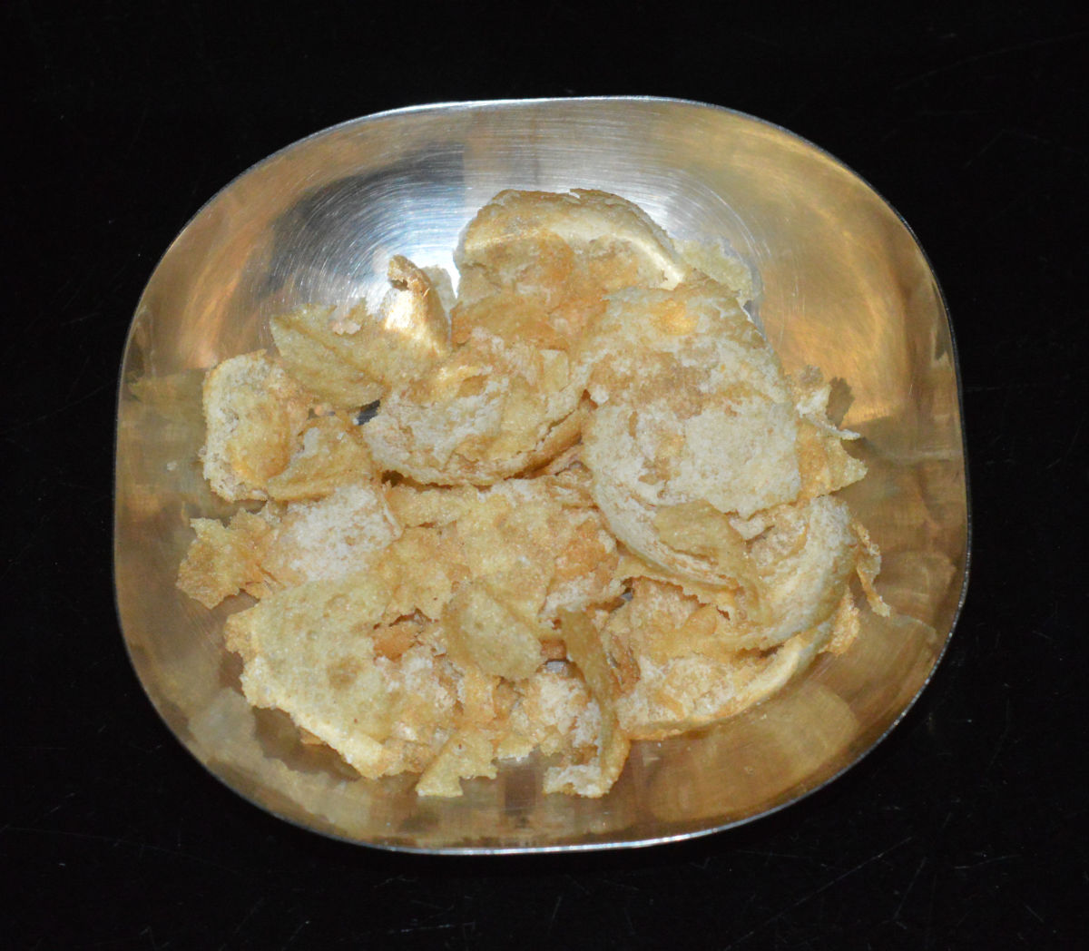 Step five: Crush 6-8 puris. Spread it on a deep bottomed plate.