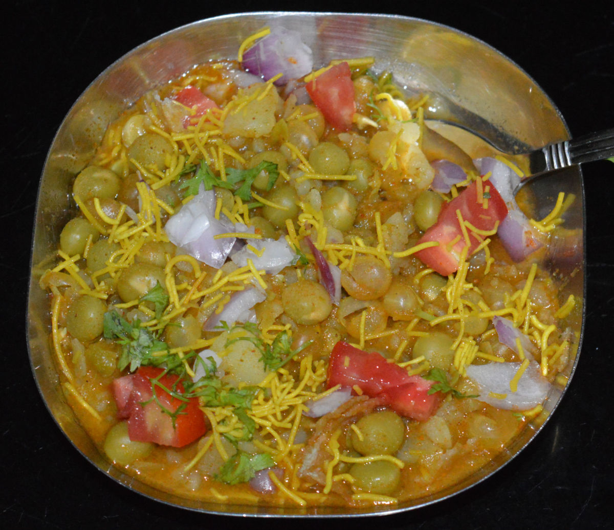 Add 4-6 tablespoons of the gravy on it. Top it with chopped onions, tomatoes, fresh coriander leaves and thin sev. Serve hot. Enjoy this healthy and delightful snack in the evening!