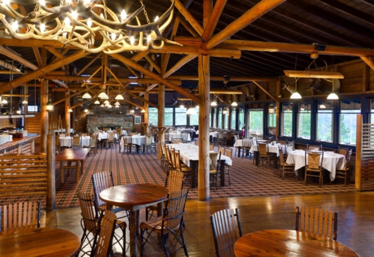 Another picture from the Grand Lake Lodge website shows the dining room with the open beams and antler chandeliers. The window on the right side open to the deck area where there are tables overlooking the lake.