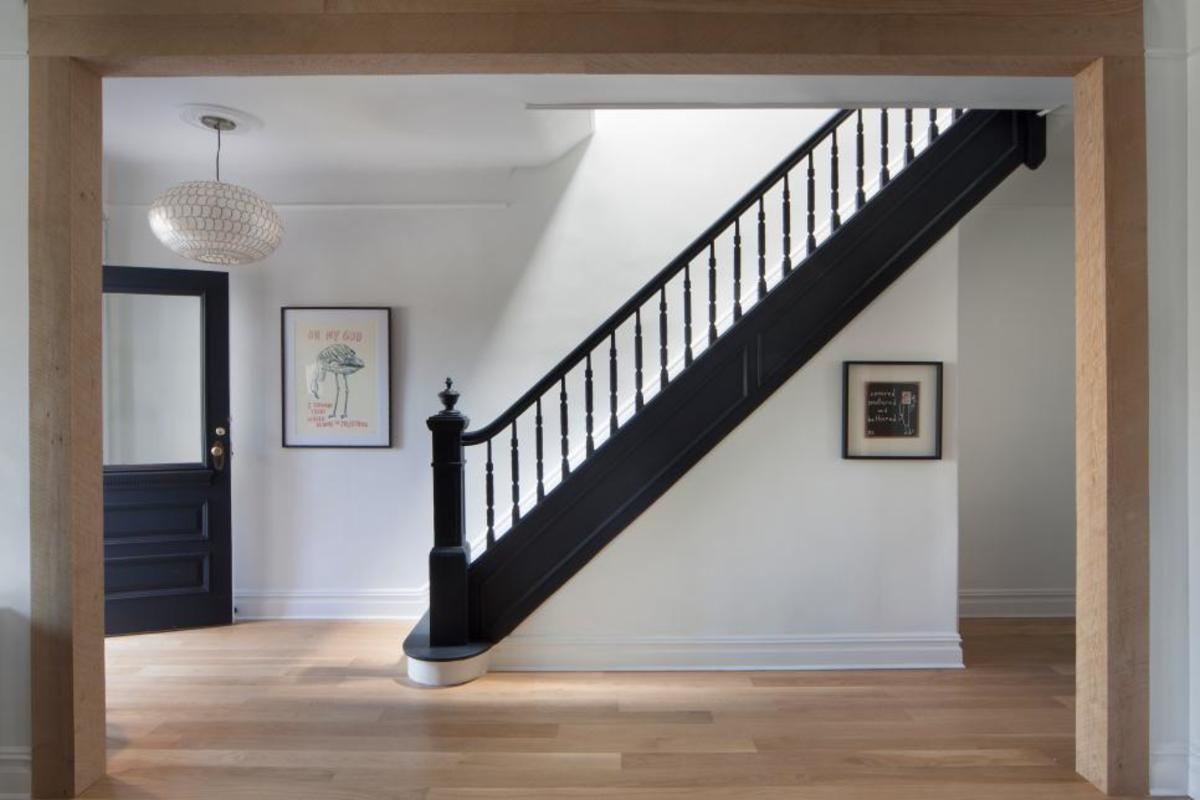 The interpretation that there is the a landing between the bottom riser of a set of steps and a door. In other words one should not be forced to come down a set of steps and for a door knob while standing on the last tread.