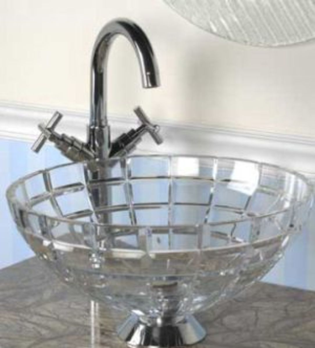 A elegant clear bathroom basin that appears to be cut glass with a two handle faucet.A clean bathroom sink basin could be visually clean and yet not be sanitized.