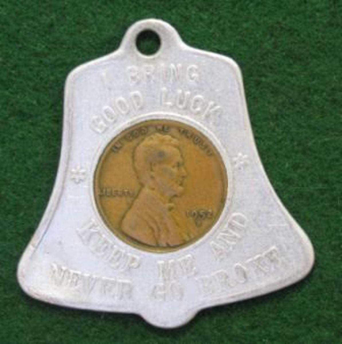 """1952-D cent inside a bell-shaped holder. The obverse reads, """"I BRING GOOD LUCK/KEEP ME AND NEVER GO BROKE."""" The hole at the top allows it to be used as a key chain fob."""