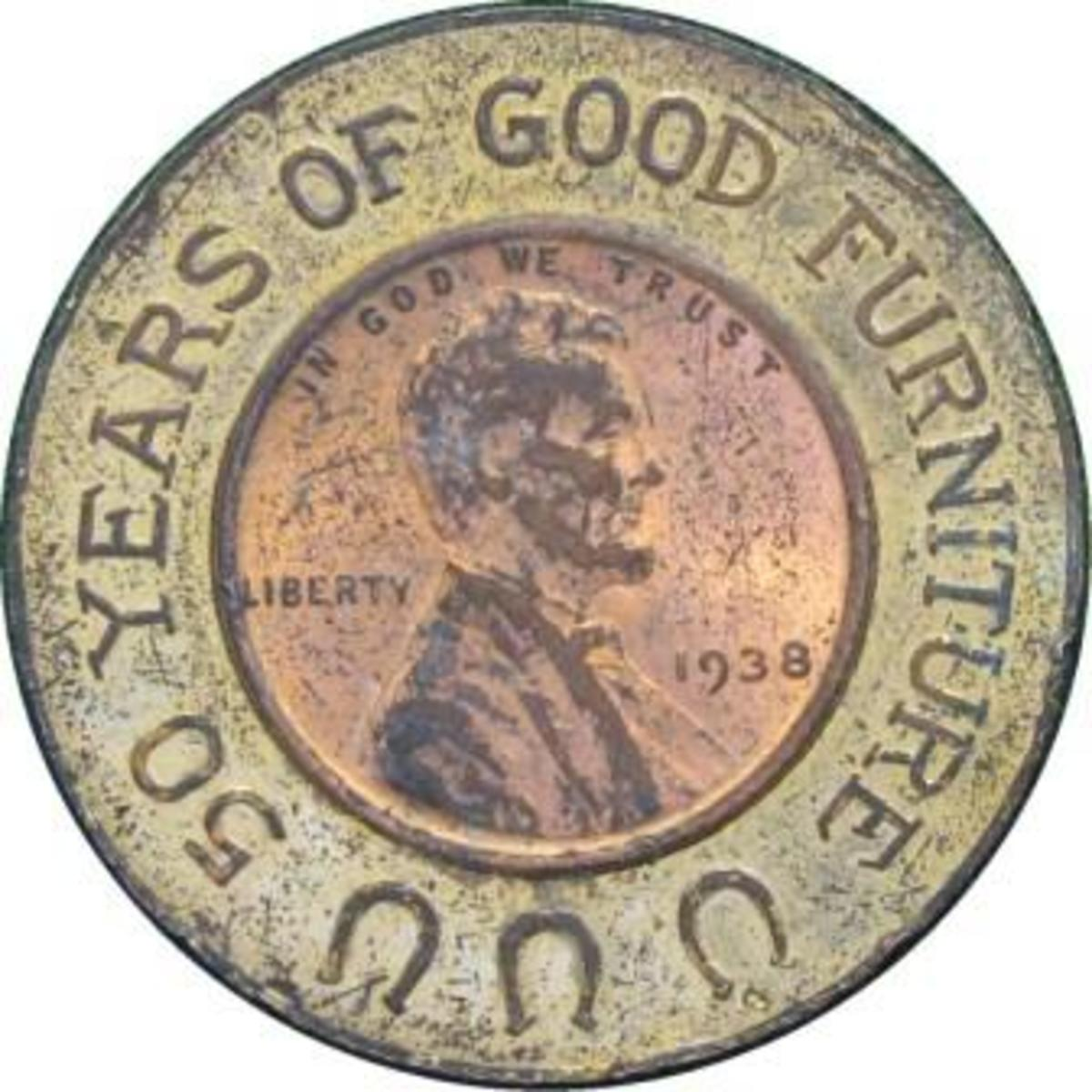 """1938 Lincoln cent encased in a brass holder. The obverse features three horseshoes and the legend, """"50 YEARS OF GOOD FURNITURE."""""""