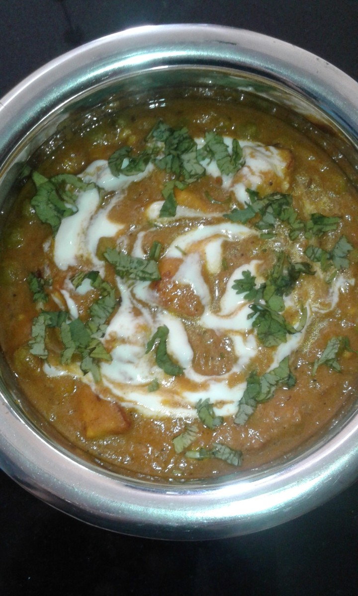 Yummy matar paneer garnished with cream and coriander leaves