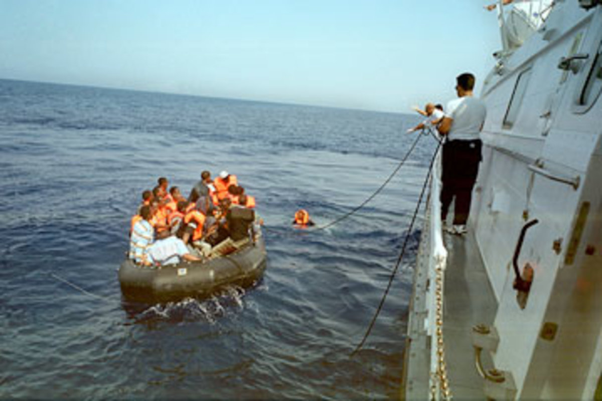 An overloaded inflatable is intercepted by the Italian Coast Guard.