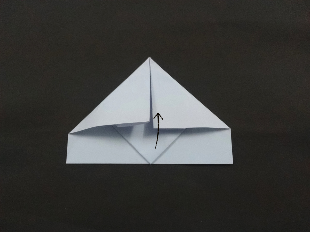 The head of the triangle visible below the folded corners. You need to pull the tip of head upwards as shown.