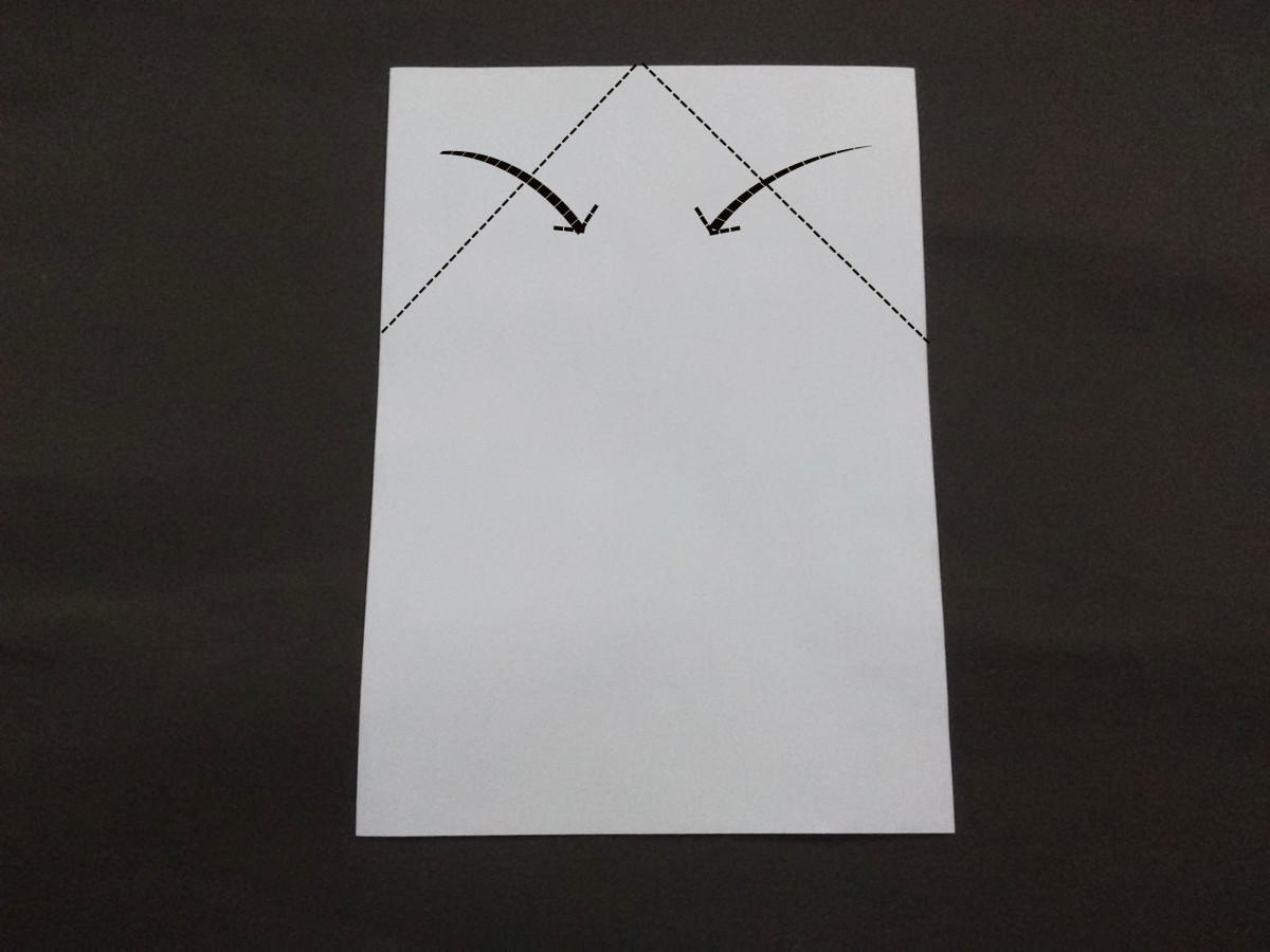 Then fold the two upper corners of the paper as shown so that the folds meet at the middle.