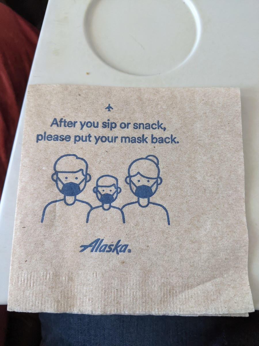 Napkin accompanying snack on Alaska Airlines.  Despite CDC advisory individual businesses as well as state and local government regulations can still require everyone, including those vaccinated, to continue to wear masks.