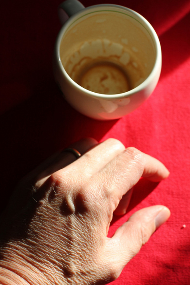 Old man's hand and empty cup of coffee
