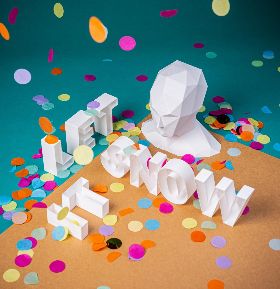 """Paper sculpture of head and words saying """"Let it snow""""."""