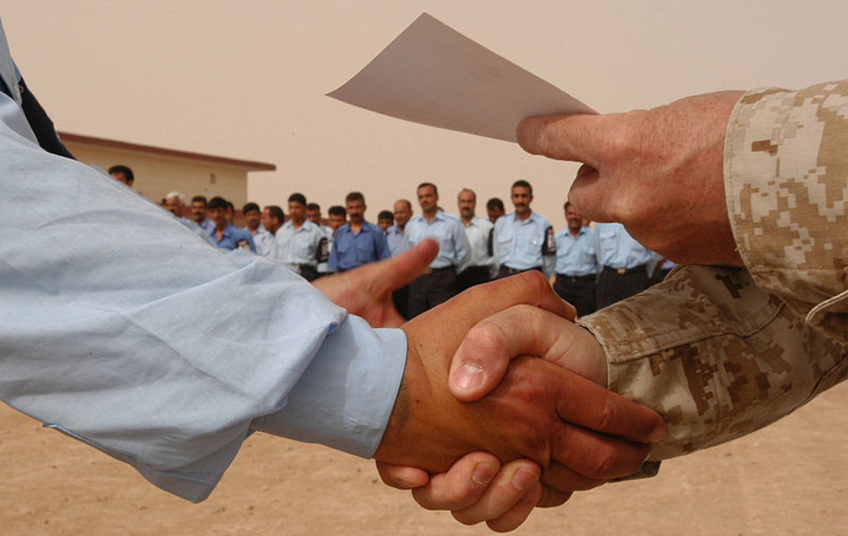 Marine shakes hands with newly graduated Iraqi policeman.--wikimedia commons