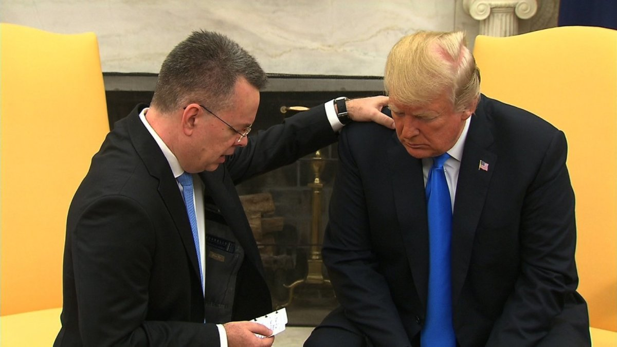Pastor Andrew Brunson praying with President Trump
