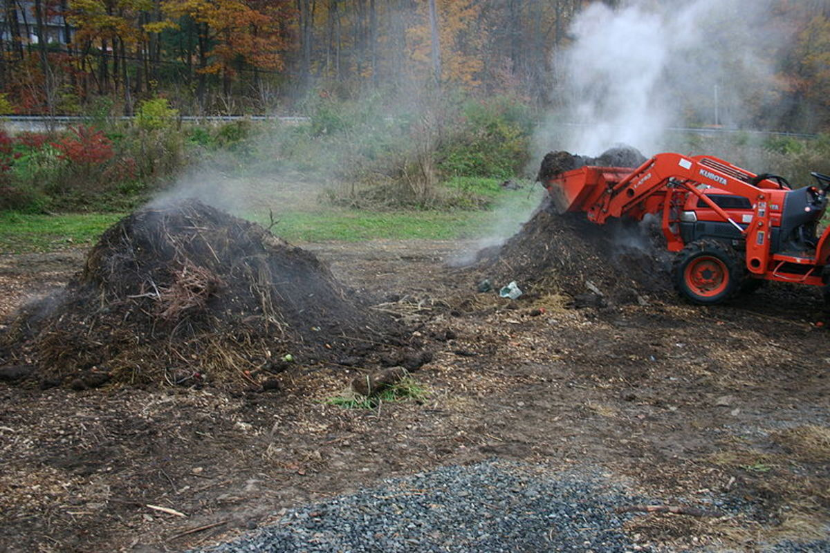 A compost pile being flipped and giving off heat in the form of steam.