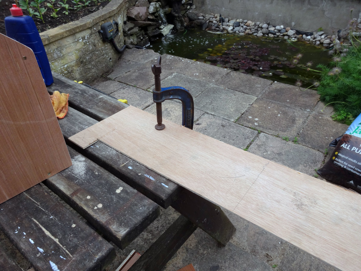 Having measured and marked out the correct dimension on the 4mm plywood clamped to the work surface, ready to cut the plywood to size for making the back.