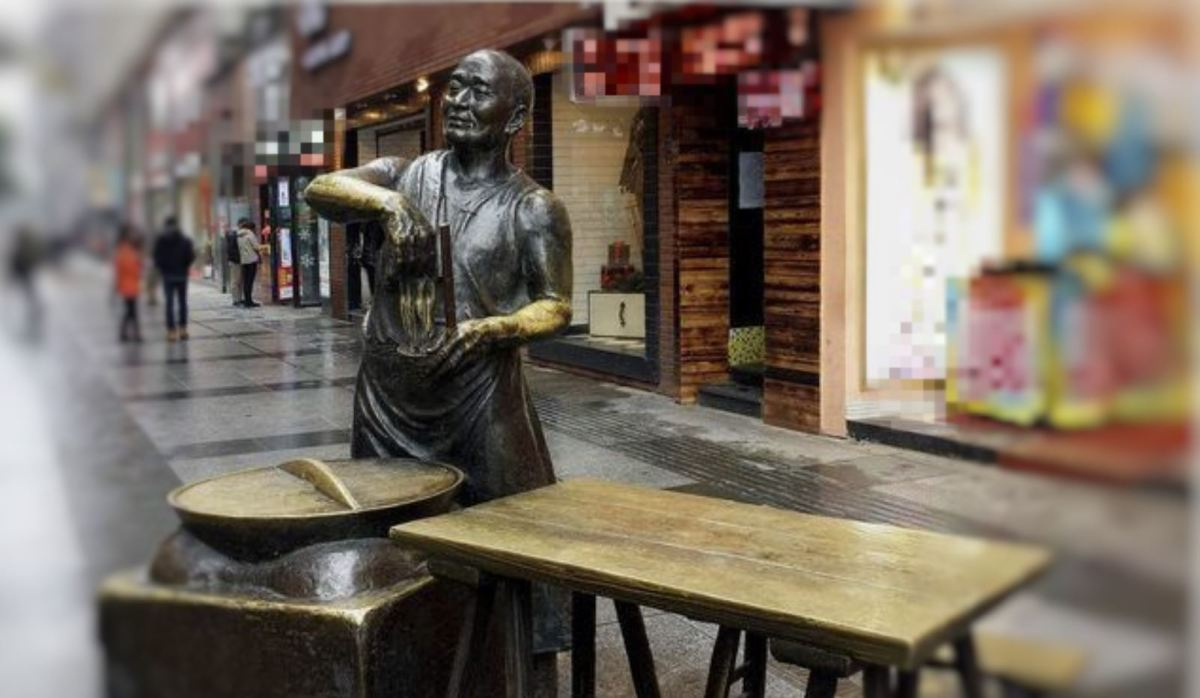 Bronze statue of the person who made hot dry noodles in Wuhan Jianghan street