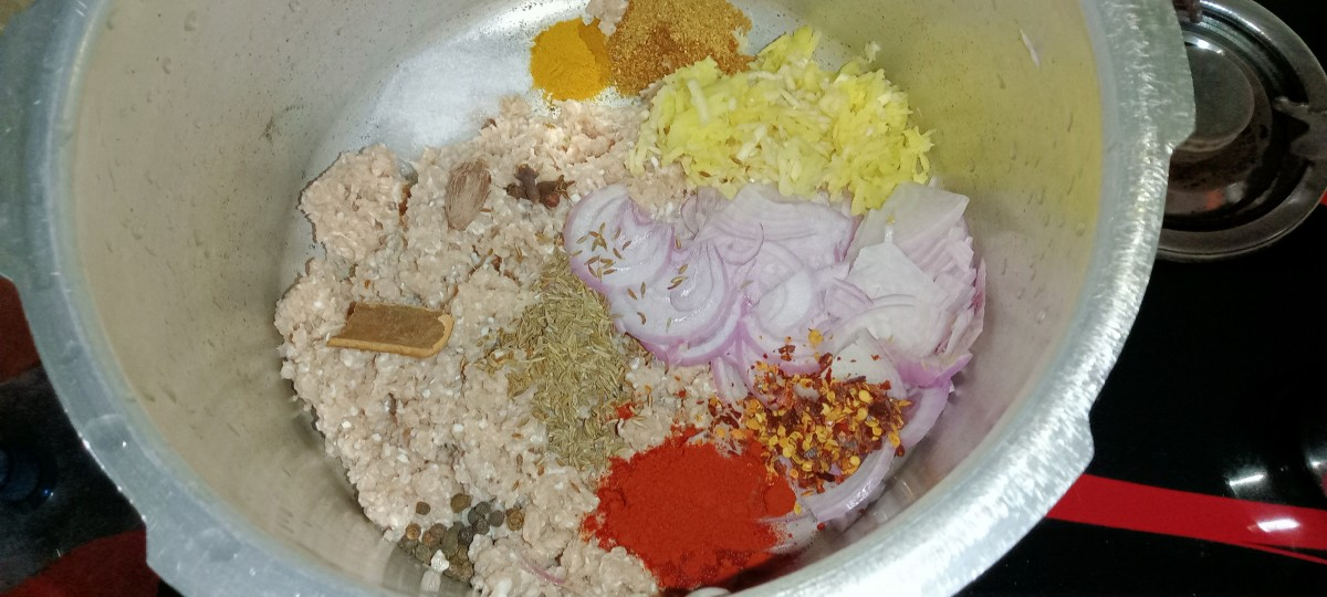 Transfer mince to a pressure cooker. Add thinly sliced onion, grated garlic and ginger, cumin seeds, black pepper, cloves, cinnamon stick, black cardamom, salt, red chilli flakes, turmeric powder, coriander powder and red chilli powder.
