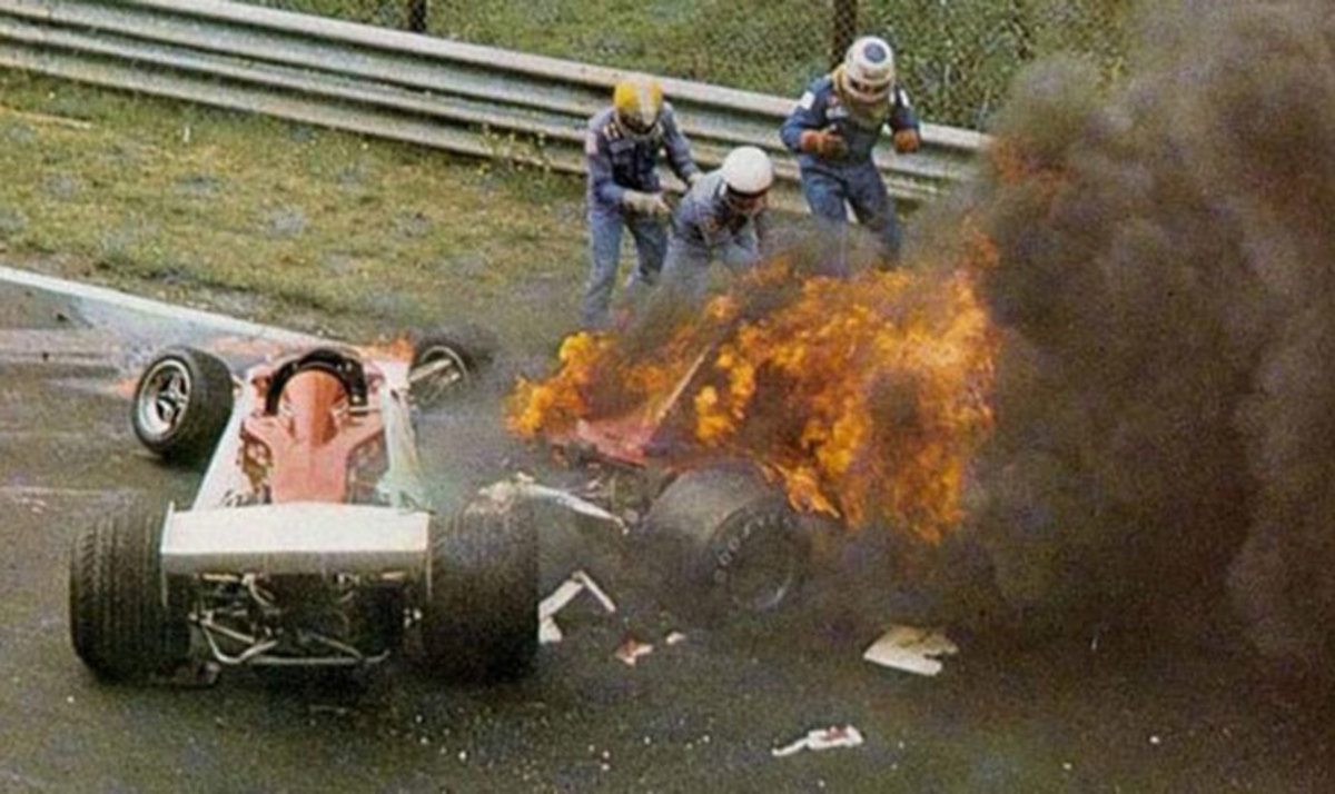 Fellow drivers fight the flames to extricate Niki Lauda from his car.