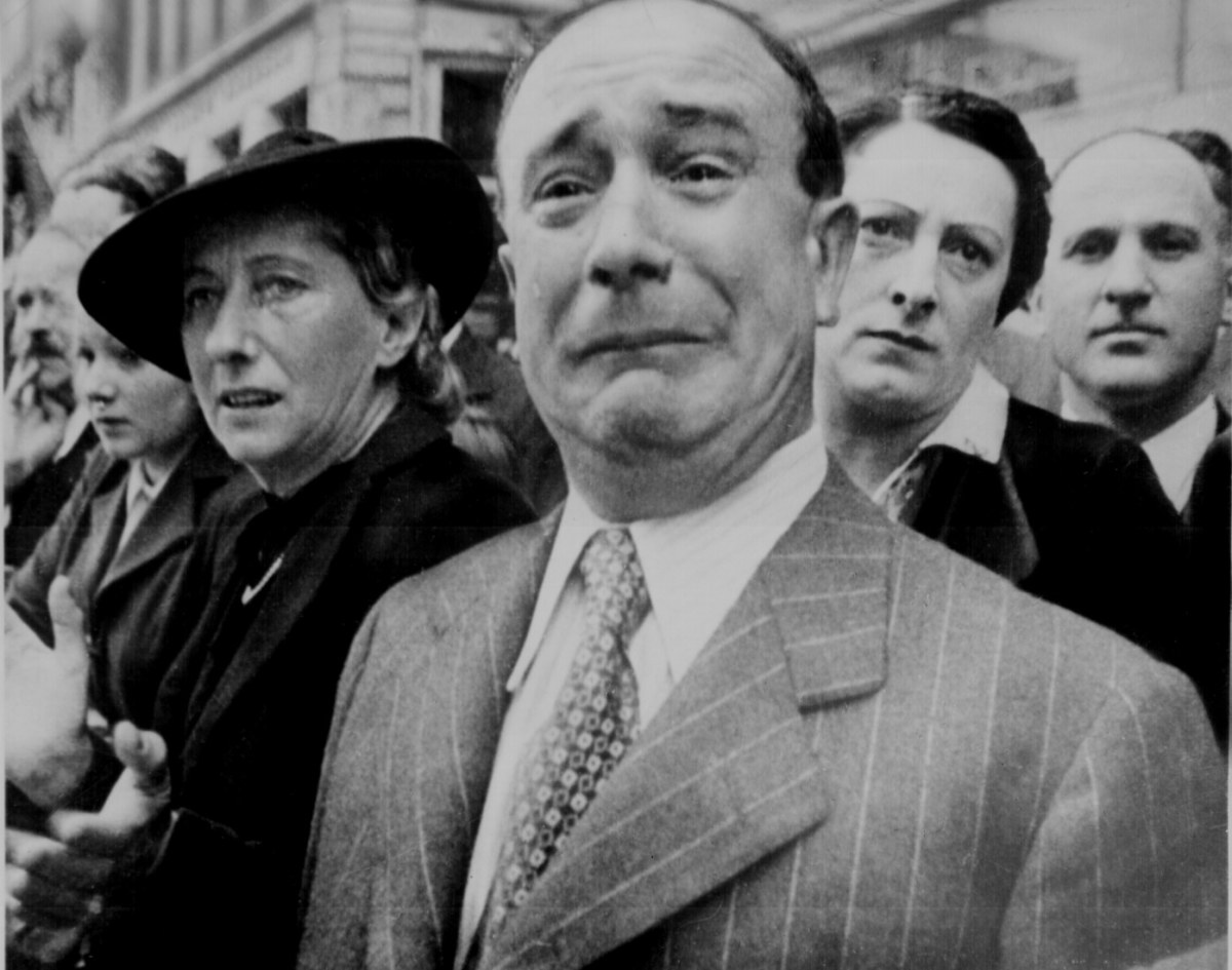 National Archives - A French man reacts to the German march on Paris, June 14 1940. His expression speaks volumes.