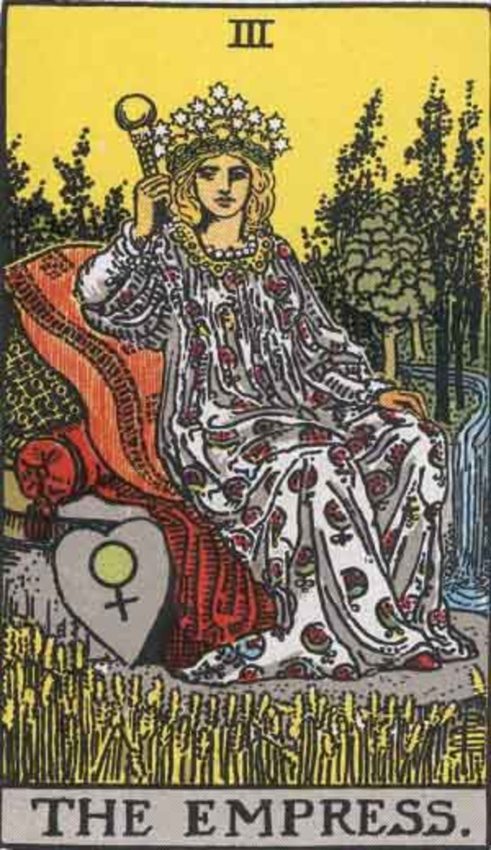 The Empress wears a crown of 12 stars, she wears a dress with a pattern of pomegranates, she has long flowing hair, a shield, a scepter, and the symbol of Venus.