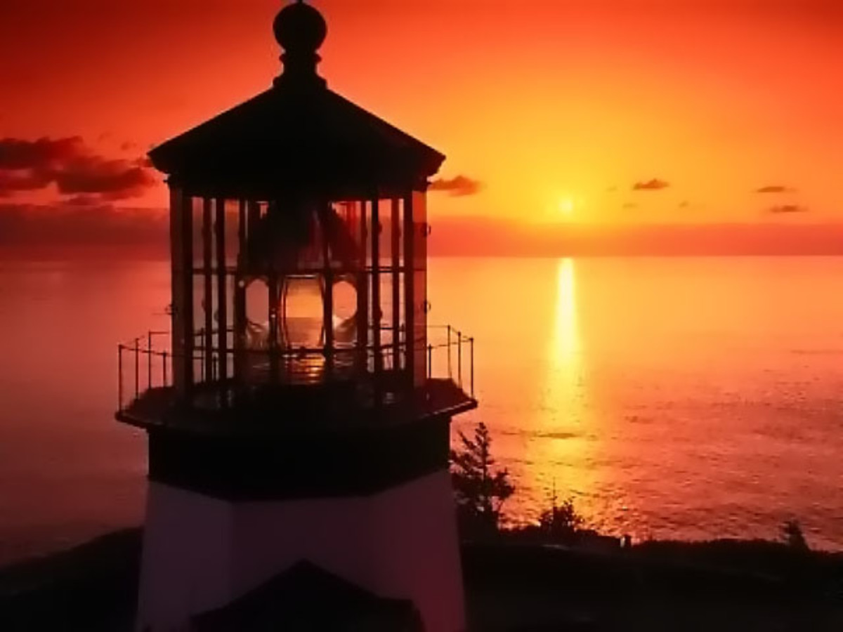 beautiful light house with a colorful yellow orange sunset