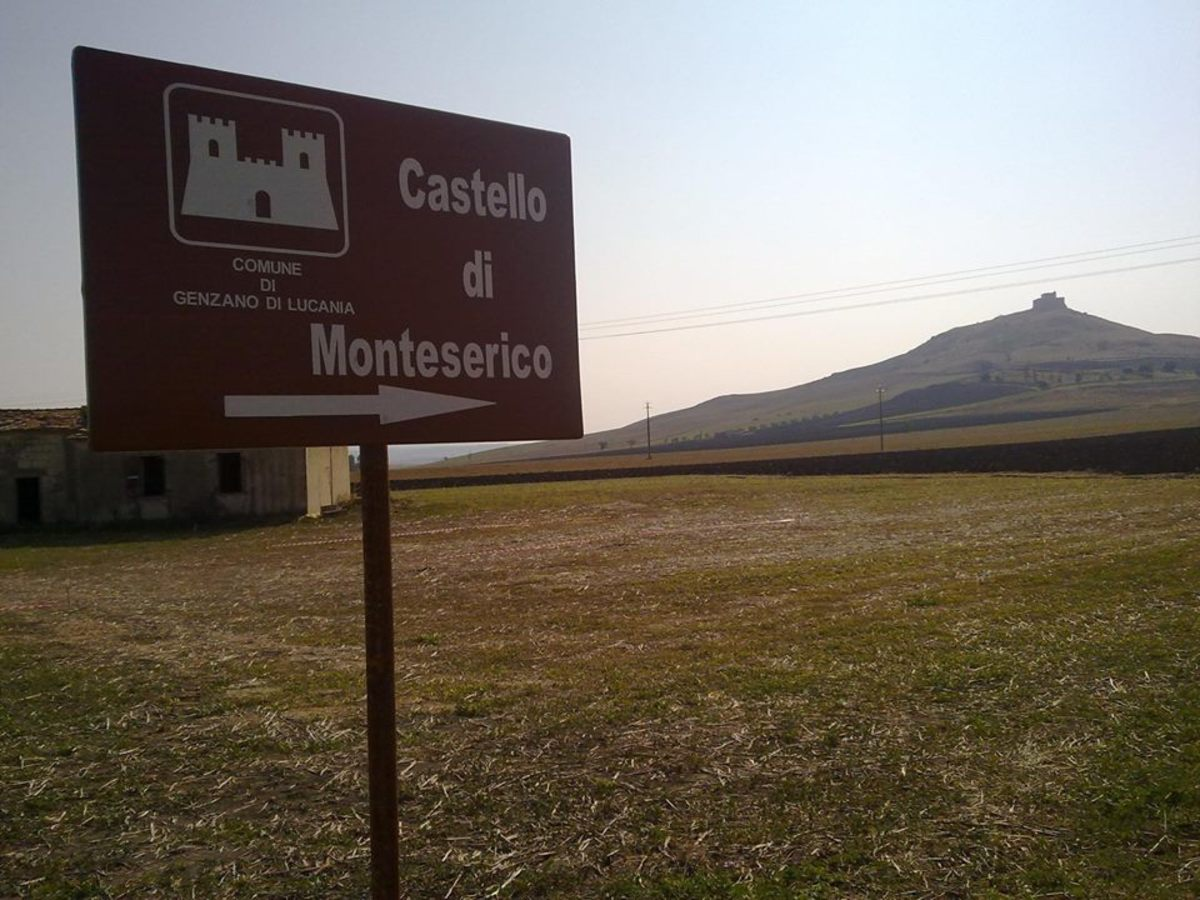 The ancient castle of Monteserico seen from far away country fields, there is also an old farm building in the picture.  Note, here above is also a map to see where Genzano and this castle are