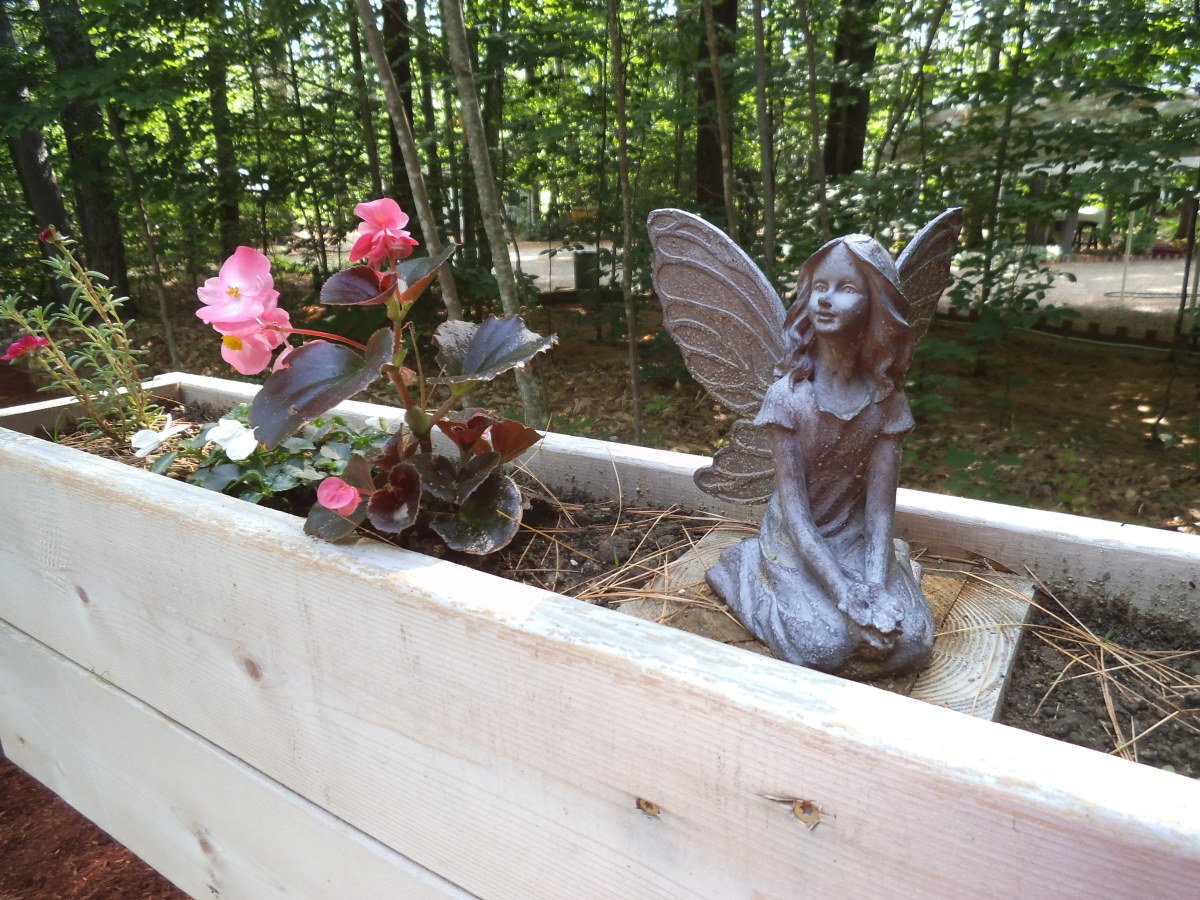 A fairy figure in a planting box.