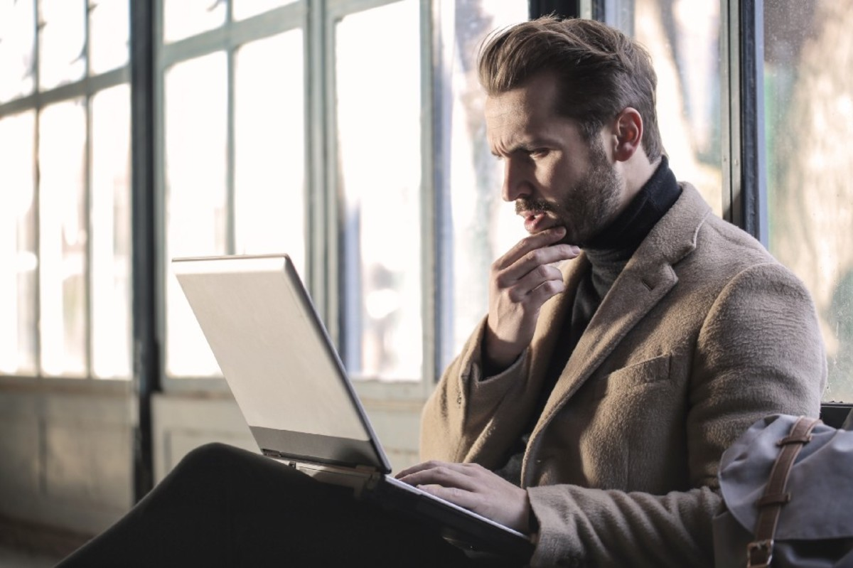A picture of a man looking at his laptop