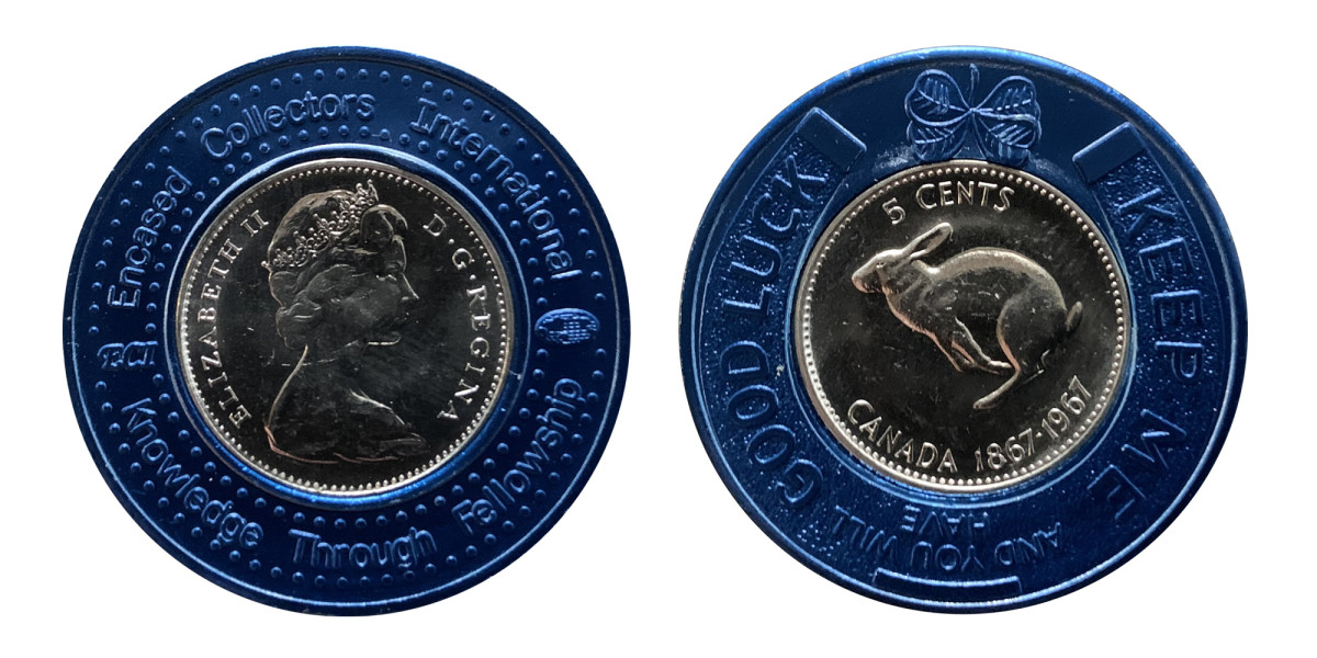 """A 1967 Canadian 5 cent coin encased in a blue colored metal encasement. Obverse: """"ENCASED COLLECTORS INTERNATIONAL - ECI - KNOWLEDGE THROUGH FELLOWSHIP."""" Reverse: """"KEEP ME AND YOU WILL HAVE GOOD LUCK."""""""