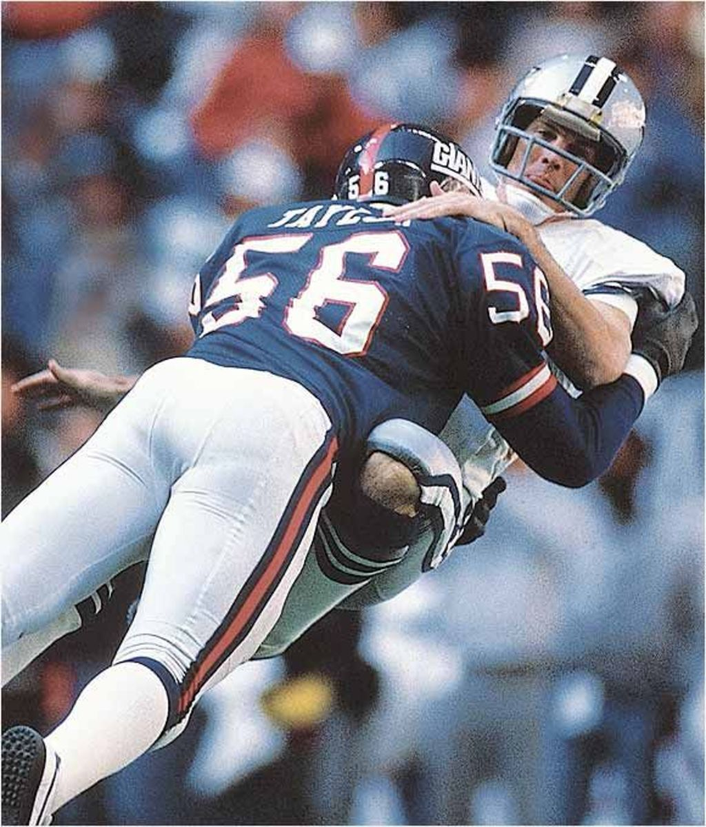 Lawrence Taylor drives a quarterback into the ground on a sack.